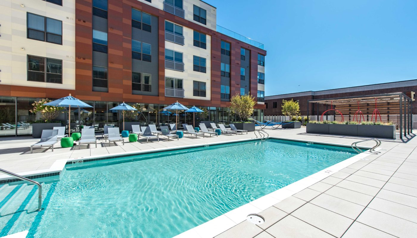 j malden center resort style pool with chaise lounge chairs, umbrellas, cocktail tables, and view of apartments and swing chairs in the background - jefferson apartment group