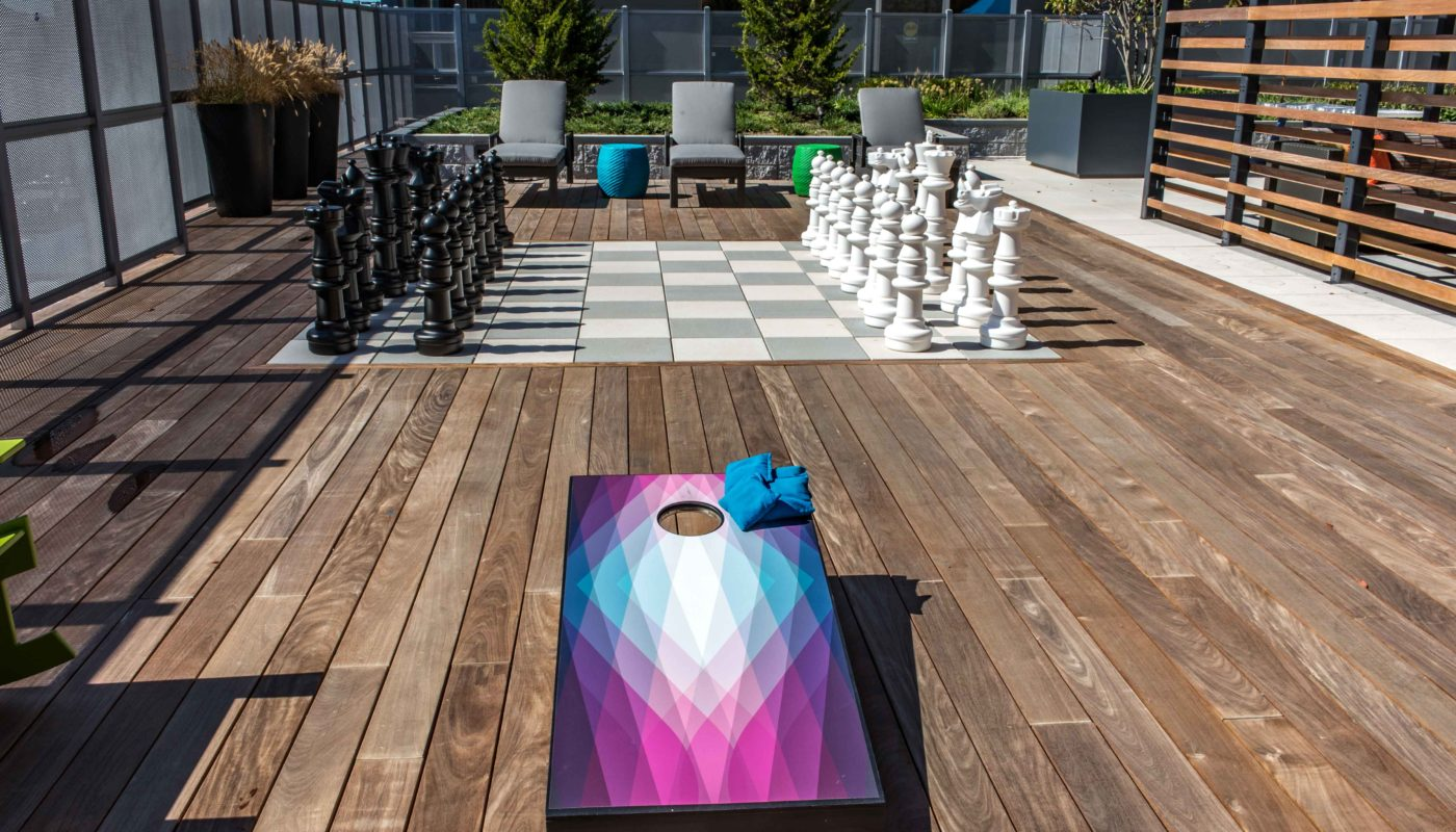 j malden center outdoor gaming area with corn hole boards and giant chess board - jefferson apartment group