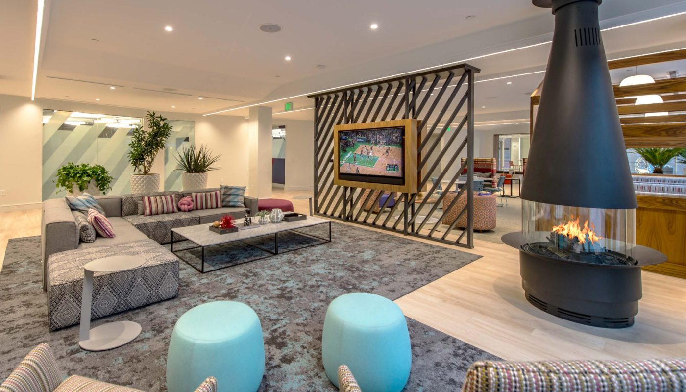 j malden center Clubroom lounge with seating, tv and fireplace - Jefferson Apartment Group