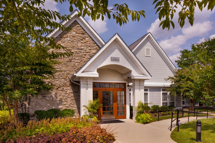 arbors at broadlands clubhouse with lush landscaping, trees and blue sky - jefferson apartment group