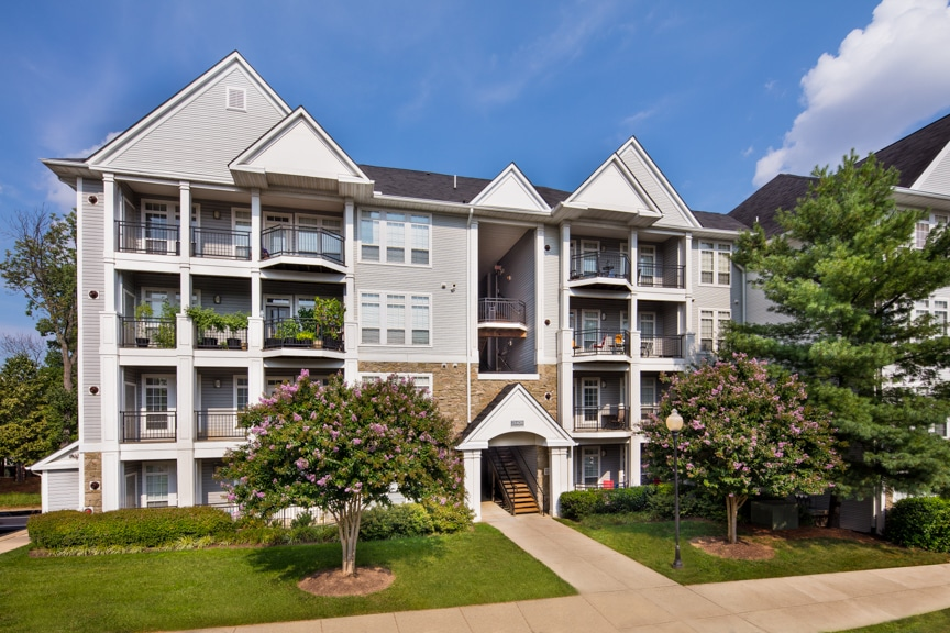 arbors at broadlands exterior showing a four story building with balconies, stone accesnts, green landscaping, sidewalk and trees - jefferson apartment group