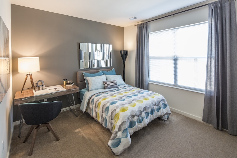 emblem bedroom with bed, desk, modern lighting and large windows - jefferson apartment group