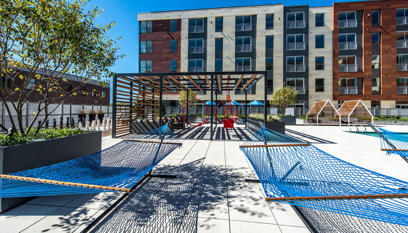 j malden center hammocks next to resort style pool and red swing chairs with apartment building in the background - jefferson apartment group