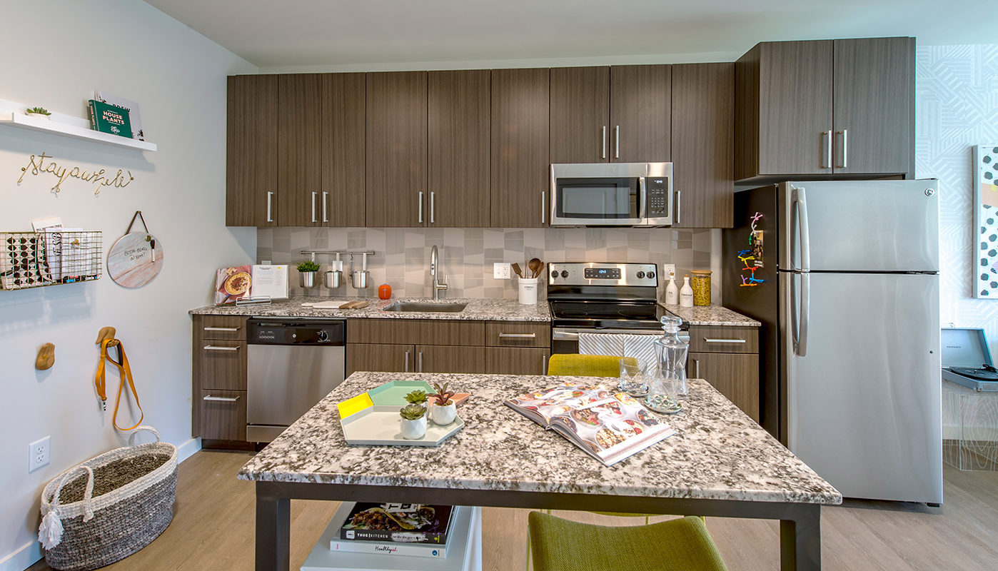 j malden center kitchen with stainless steel appliances, granite countertops, sleek plank flooring and movable island - jefferson apartment group