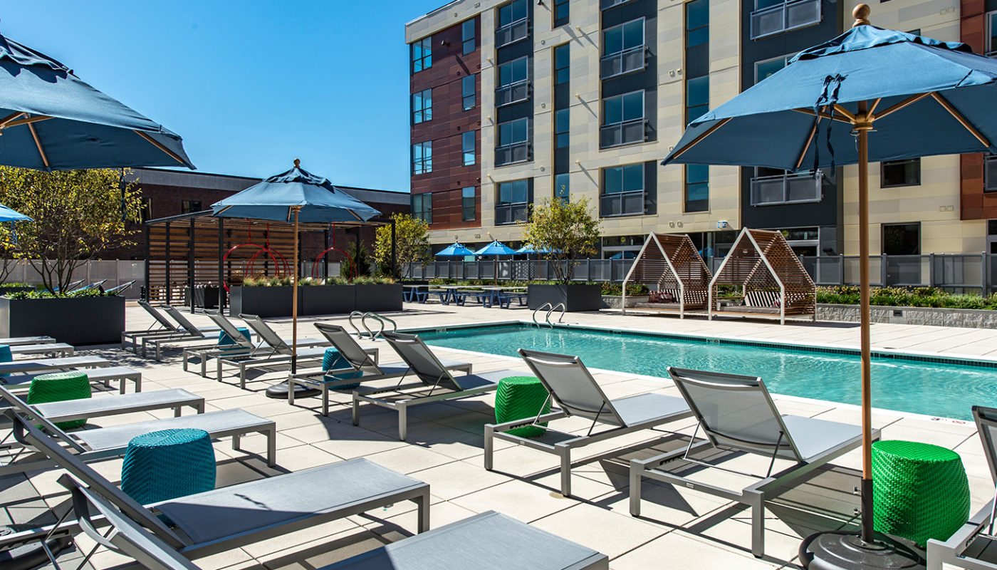 j malden center resort style pool with chaise lounge chairs, umbrellas, cocktail tables and view of apartment building in the background - jefferson apartment group