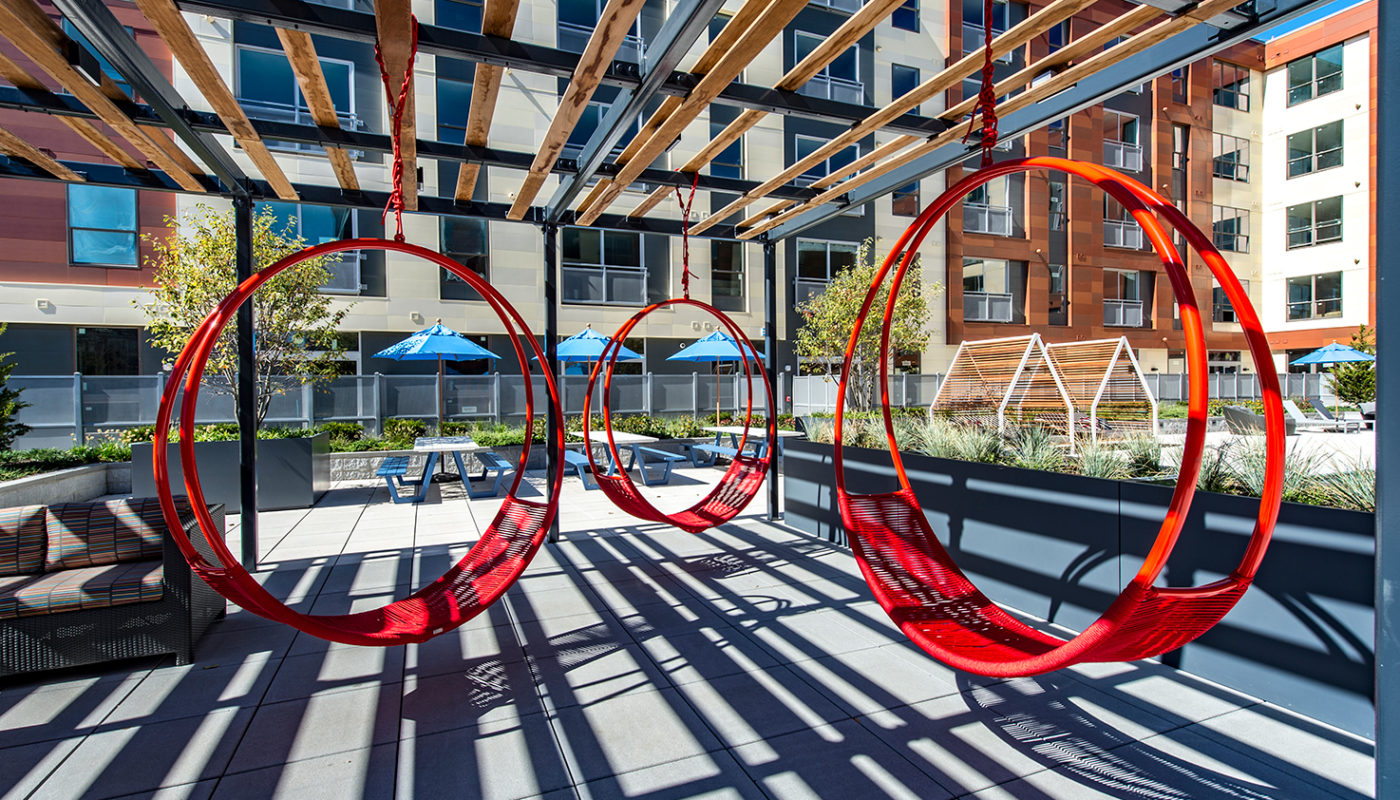 j malden center red swing chairs under pergola with view of picnic tables, chairs and apartment building in the background - jefferson apartment group