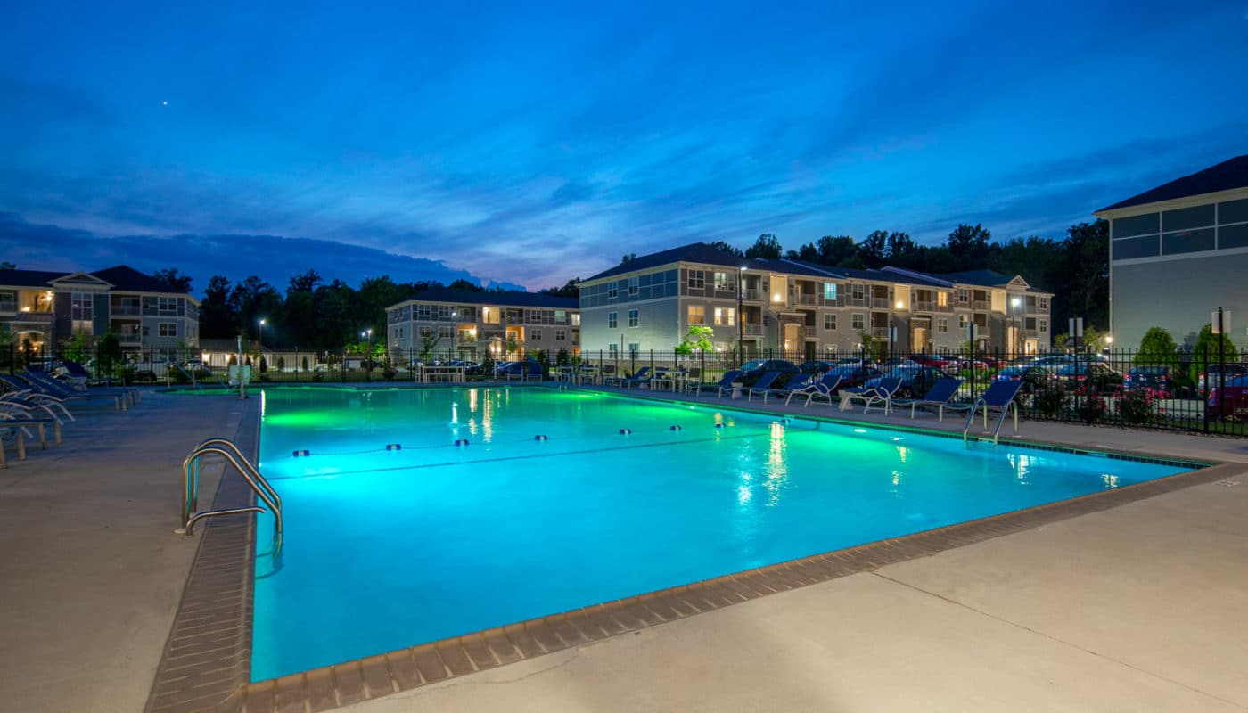 emblem at christiana resort style pool at night with chaise lounge chairs, and view of apartment buildings in the background - jefferson apartment group