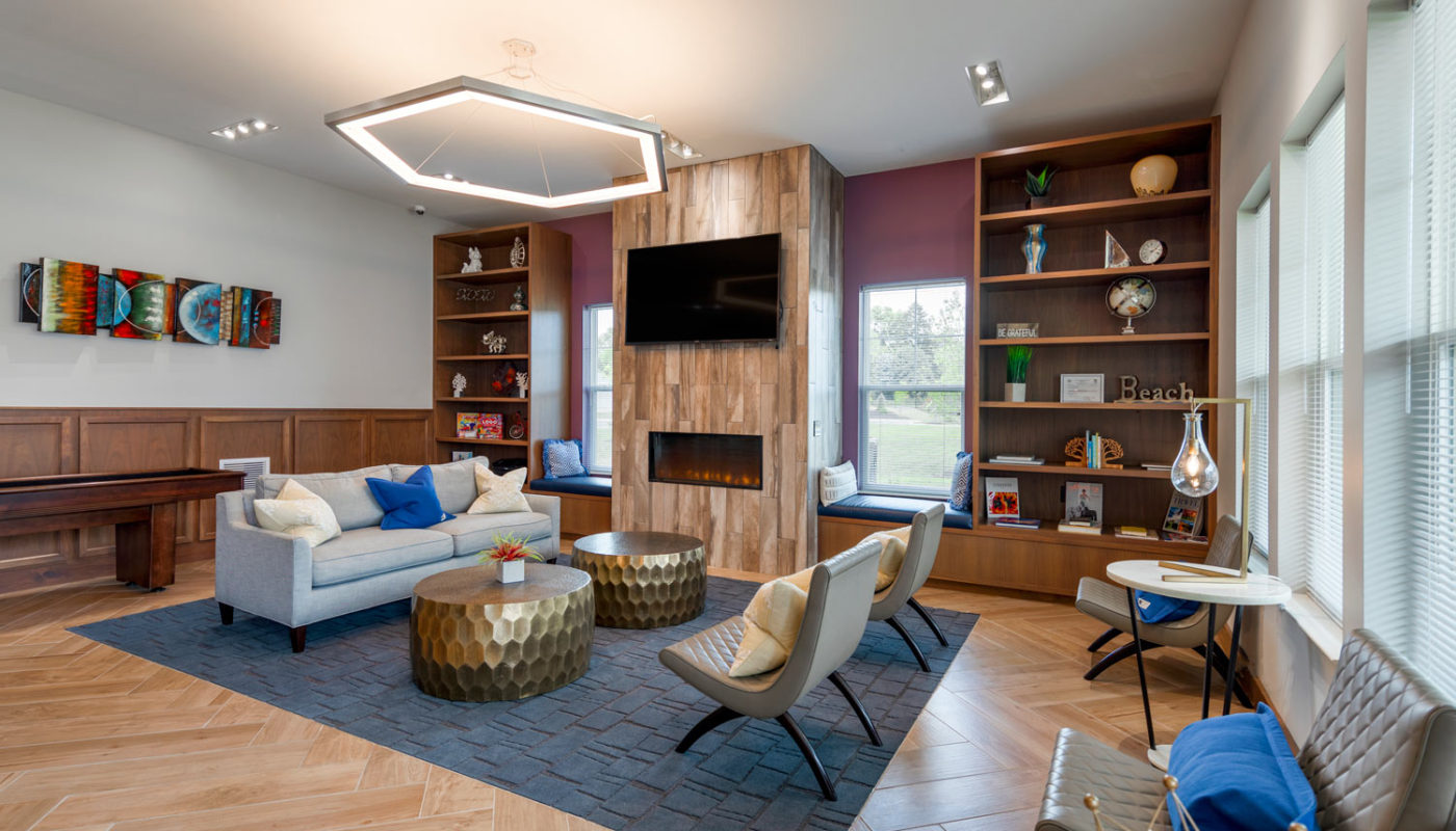 emblem resident lounge with social seating, shuffleboard table, fireplace, book shelves, modern lighting and flat screen tv - jefferson apartment group