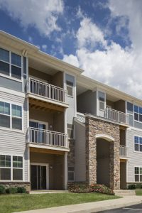 three story building with stone accents, balconies and lush green lawn - jefferson apartment group