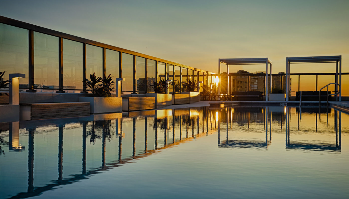 evening view of pool with planters and a view of washington dc at j sol arlington luxury apartments