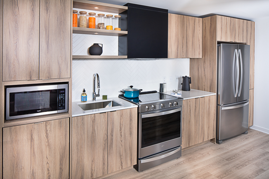 kitchen at j sol with stainless steel appliances, wood cabinetry, quartz countertops and plank flooring