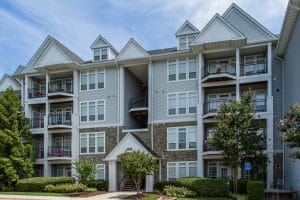arbors at broadlands exterior showing a four story building with balconies, trees, lush landscaping and stone accents - jefferson apartment group