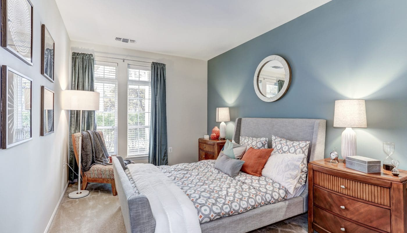 arbors at broadlands bedroom with bed, night stand, large windows and modern artwork - jefferson apartment group