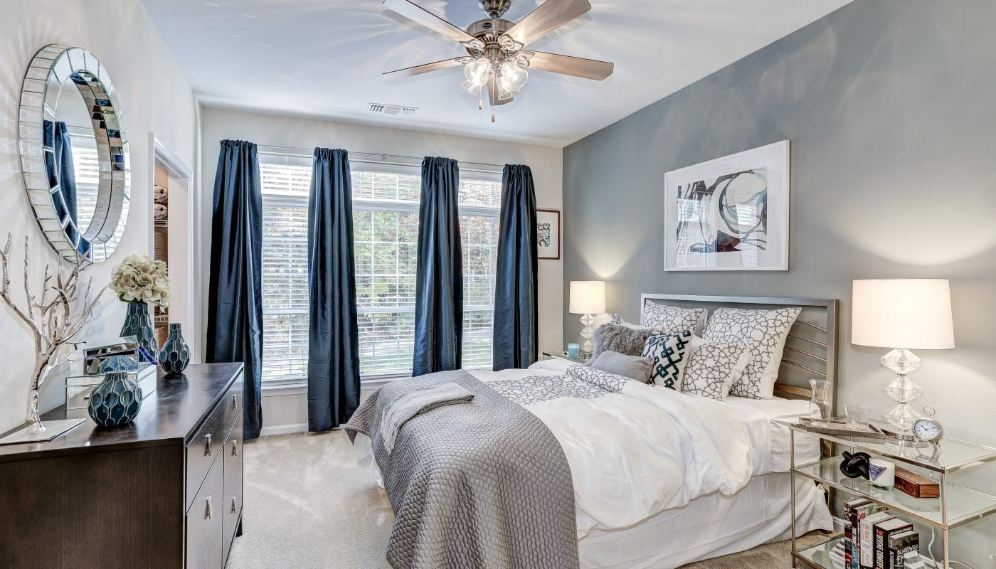 arbors at broadlands bedroom with bed, dresser, night stand, large windows, ceiling fan and modern artwork - jefferson apartment group