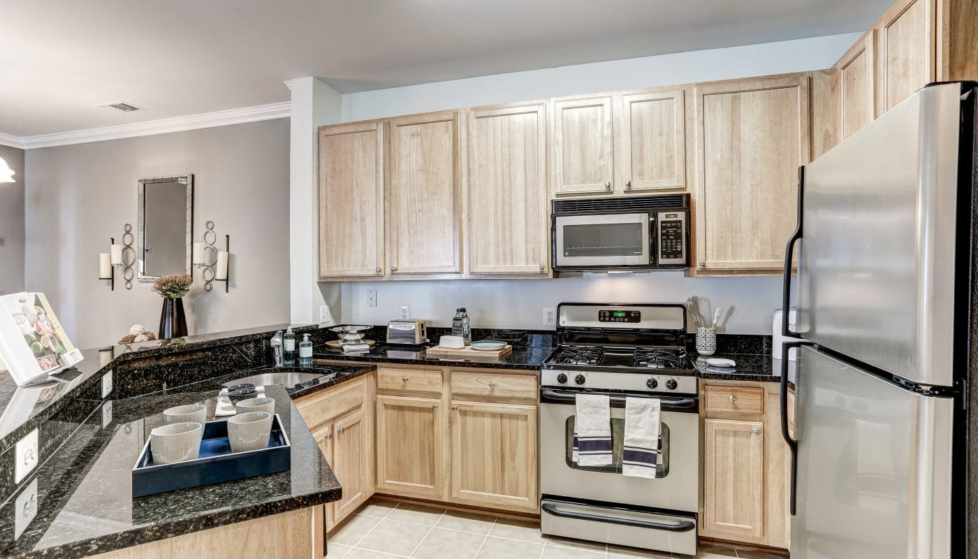 arbors at broadlands kitchen with stainless steel appliances, granite countertops, tile flooring and view of living area - jefferson apartment group