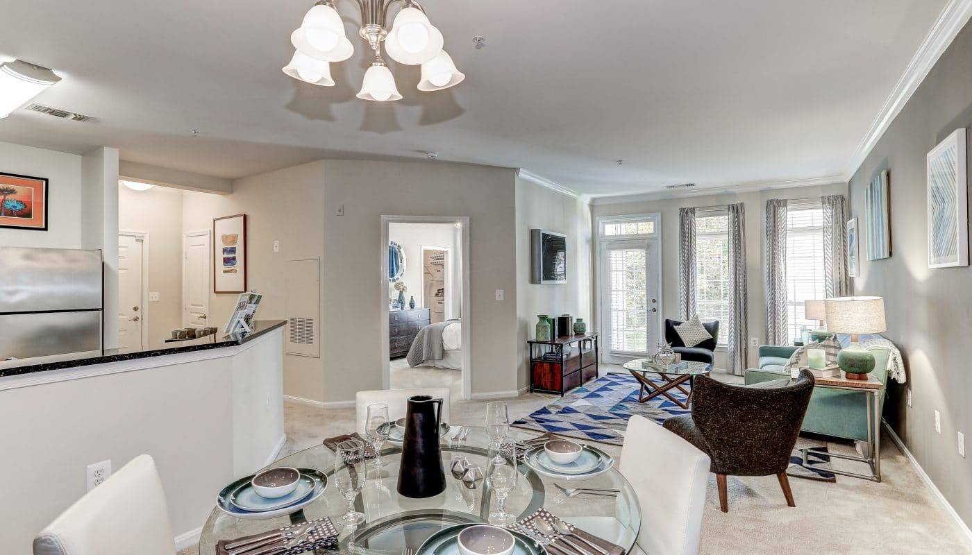 arbors at broadslands living area with couch, credenza, flat screen tv, coffee table, dining area with table, four chairs, place settings, french doors, large windows and views of kitchen and bedroom - jefferson apartment group