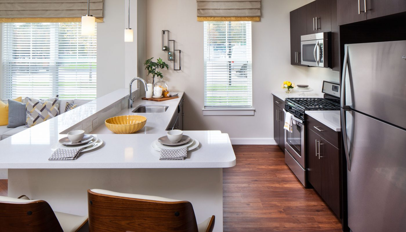 one upland kitchen area with stainless steel appliances, breakfast bar with quartz countertops, espresso cabinetry and gas range - jefferson apartment group