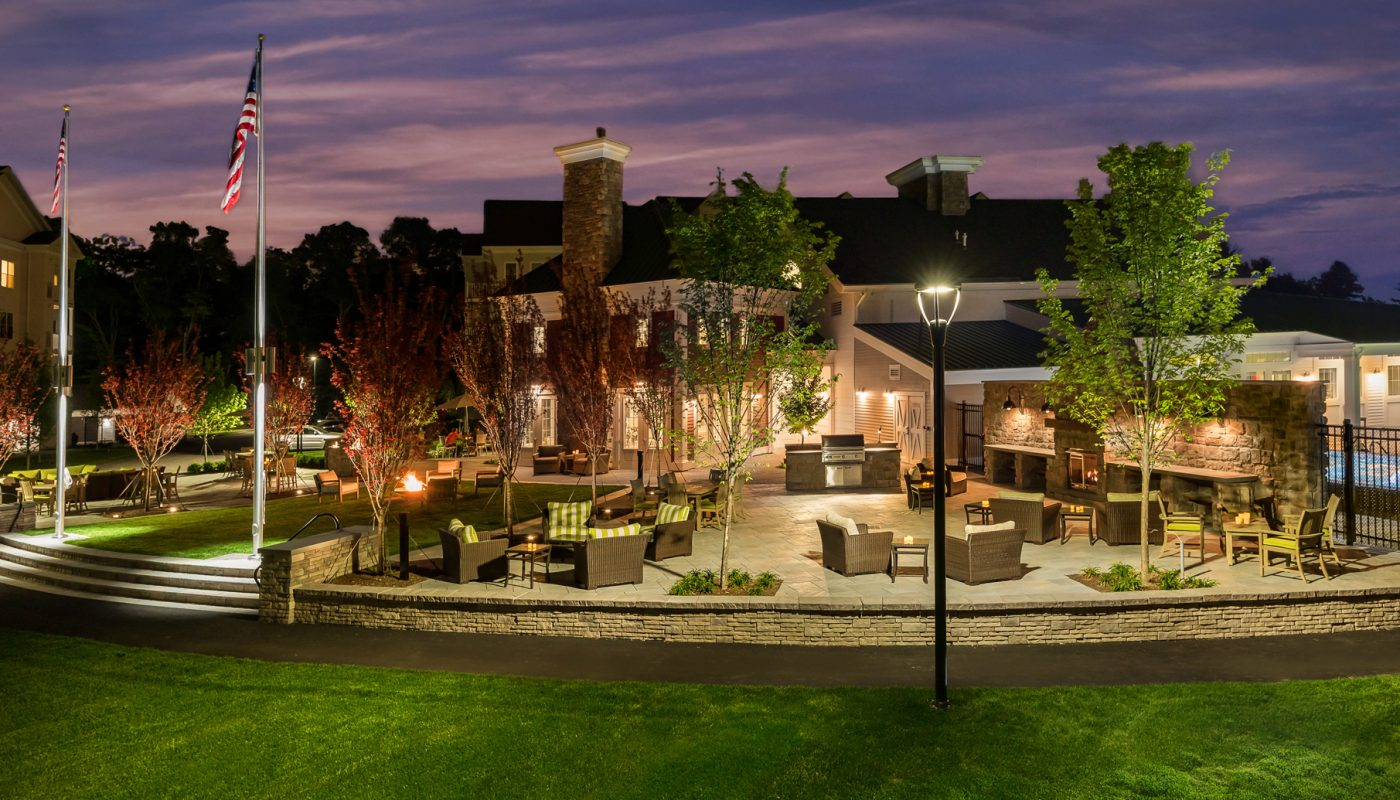 one upland outdoor living area with grilling stations, dining tables, social seating and view of apartment building in the background - jefferson apartment group