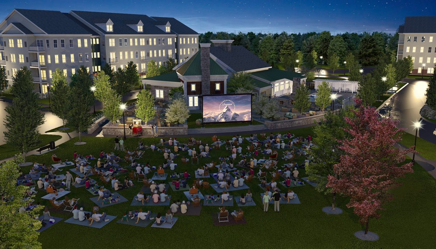 one upland outdoor movie night with large screen and many people watching on blankets and patio chairs. view of apartment building in the background - jefferson apartment group
