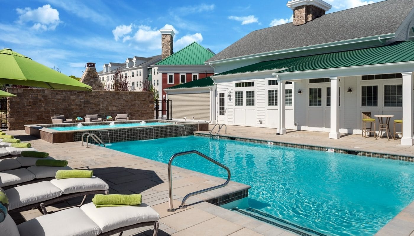 one upland resort style pool with water features, chaise lounge chairs, umbrellas and view of club house - jefferson apartment group