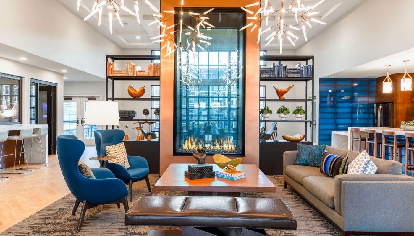 jefferson mount laurel resident club room with bar area, social seating, modern lighting and contemporary fireplace - jefferson apartment group