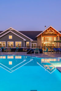 jefferson mount laurel swimming pool at dusk with chaise lounge chairs and club room in background - jefferson apartment group