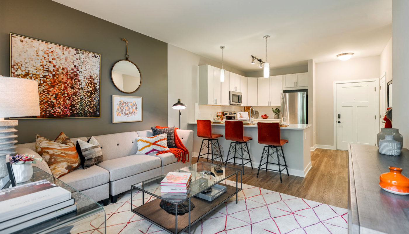jefferson mount laurel living area with couch, coffee table, modern artwork and view of kitchen with breakfast bar, stainless steel appliances, quartz countertops and modern lighting - jefferson apartment group