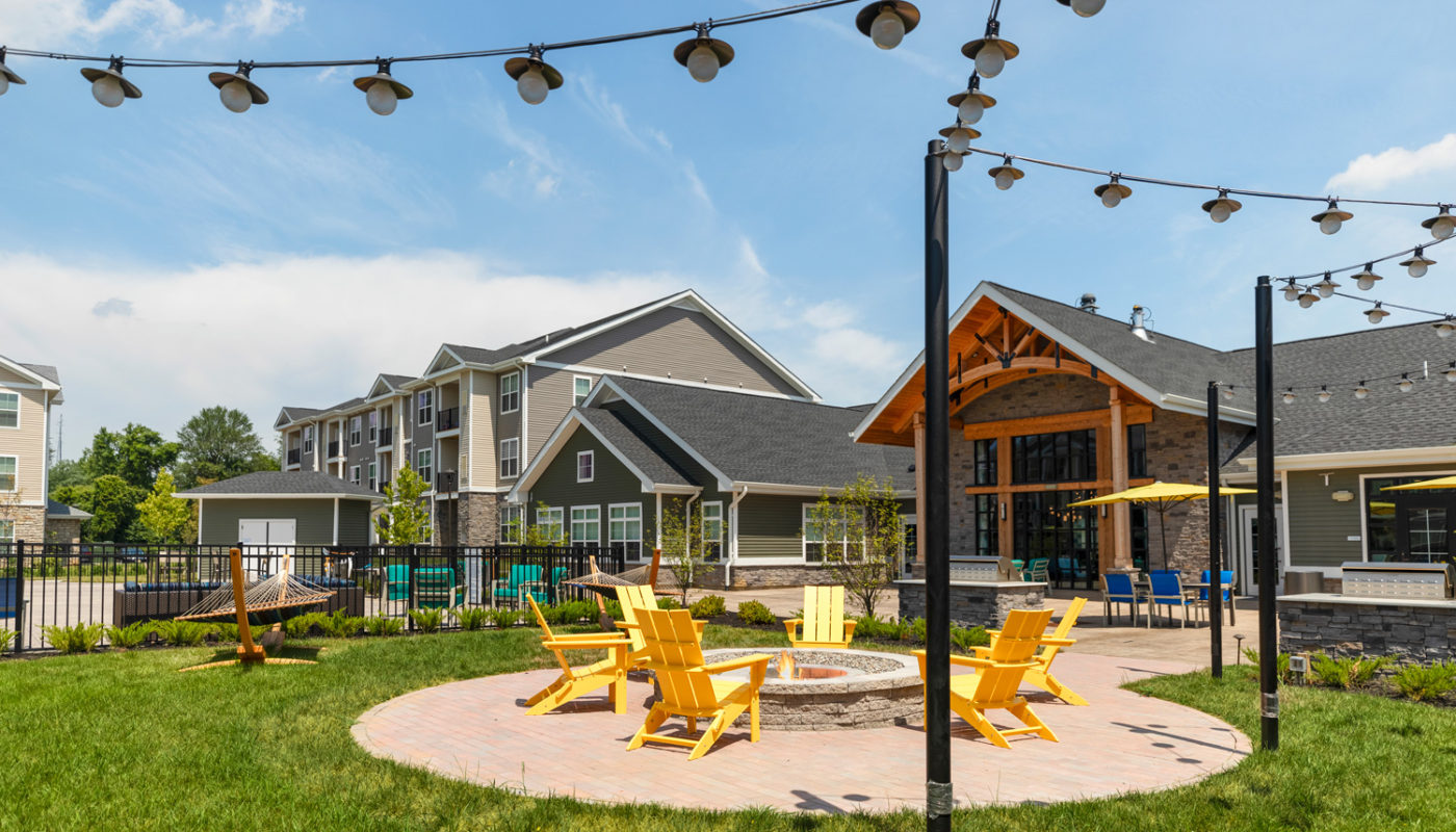 fire pit surrounded by Adirondack chairs, hammocks, and club house in the background