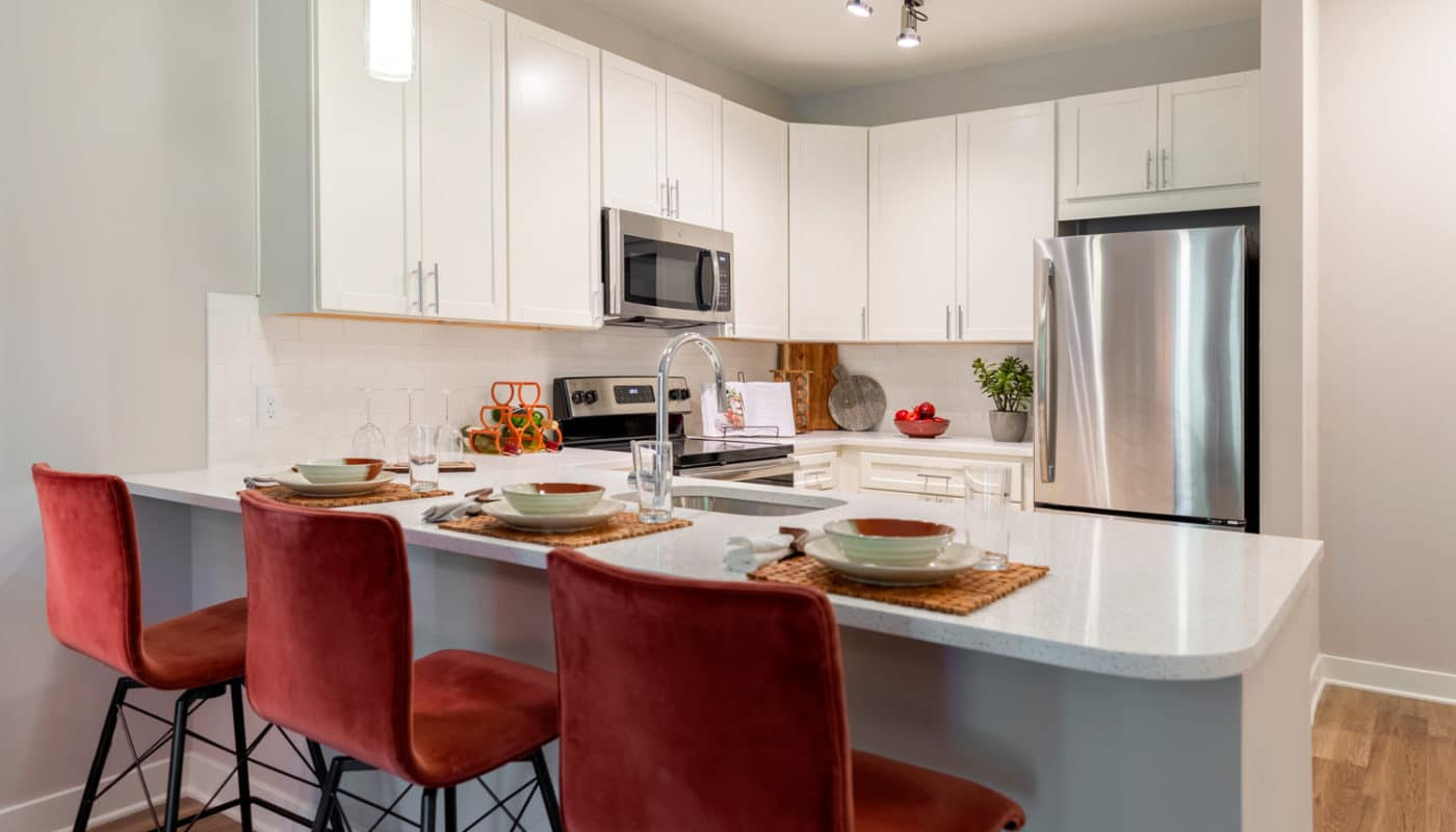jefferson mount laurel kitchen with breakfast bar, bar stools, place settings, stainless steel appliances, quartz countertops and white cabinetry - jefferson apartment group