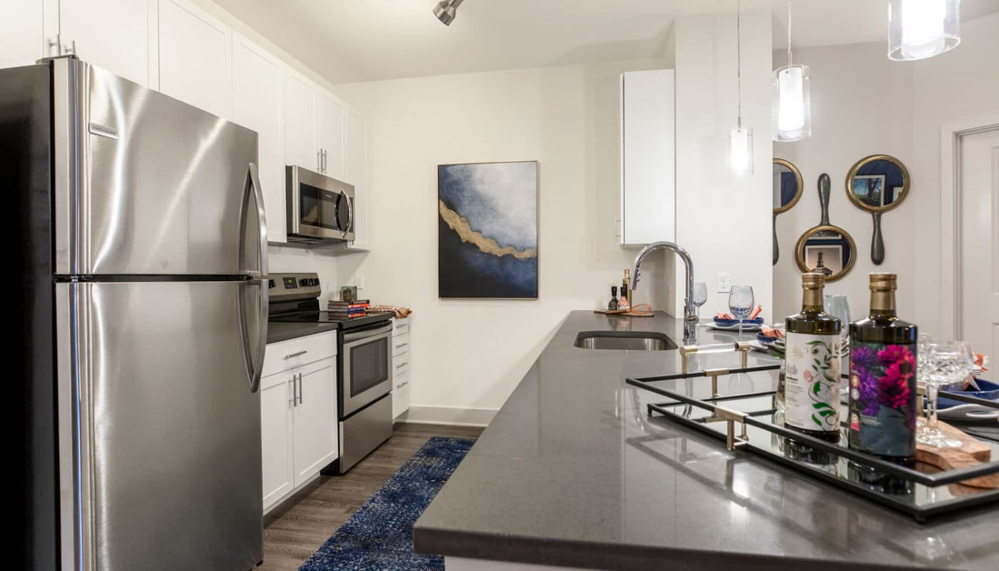 j creekside at exton luxury apartments kitchen with stainless steel appliances, quartz countertops, plank flooring, and modern artwork - jefferson apartment group