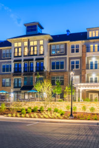 exterior of 4 story apartment building with nice landscaping at dusk