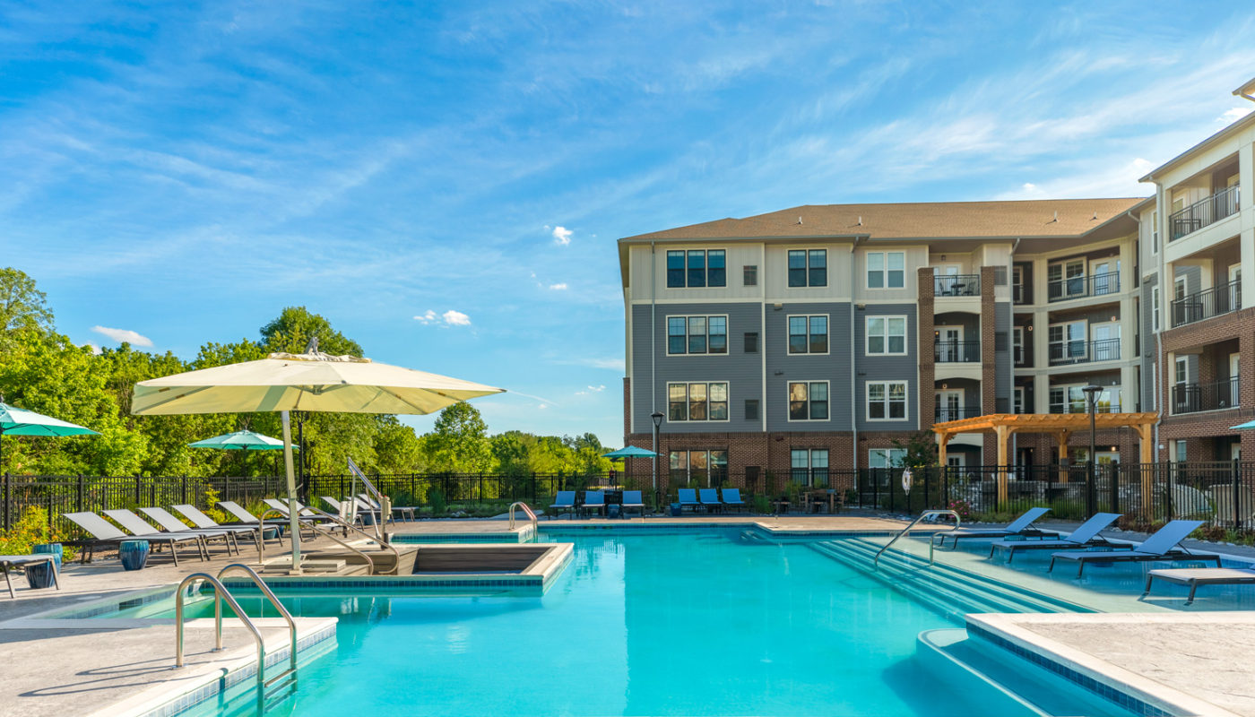 pool with lounge chairs, and umbrellas at j creekside luxury apartments in exton pa
