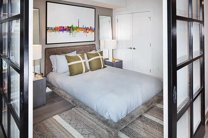 bedroom with bed, night stands decorative wall art and view of closet