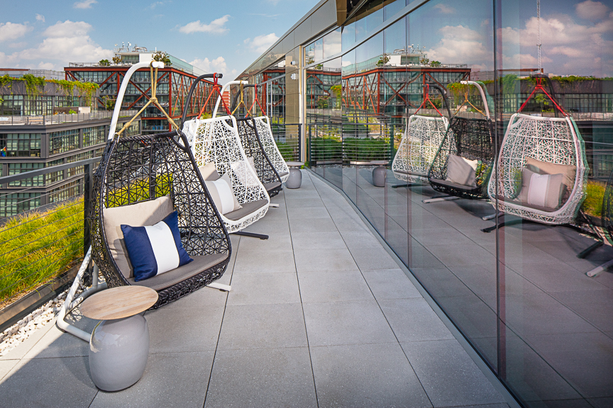 rooftop lounge swing chairs with view of city in the background