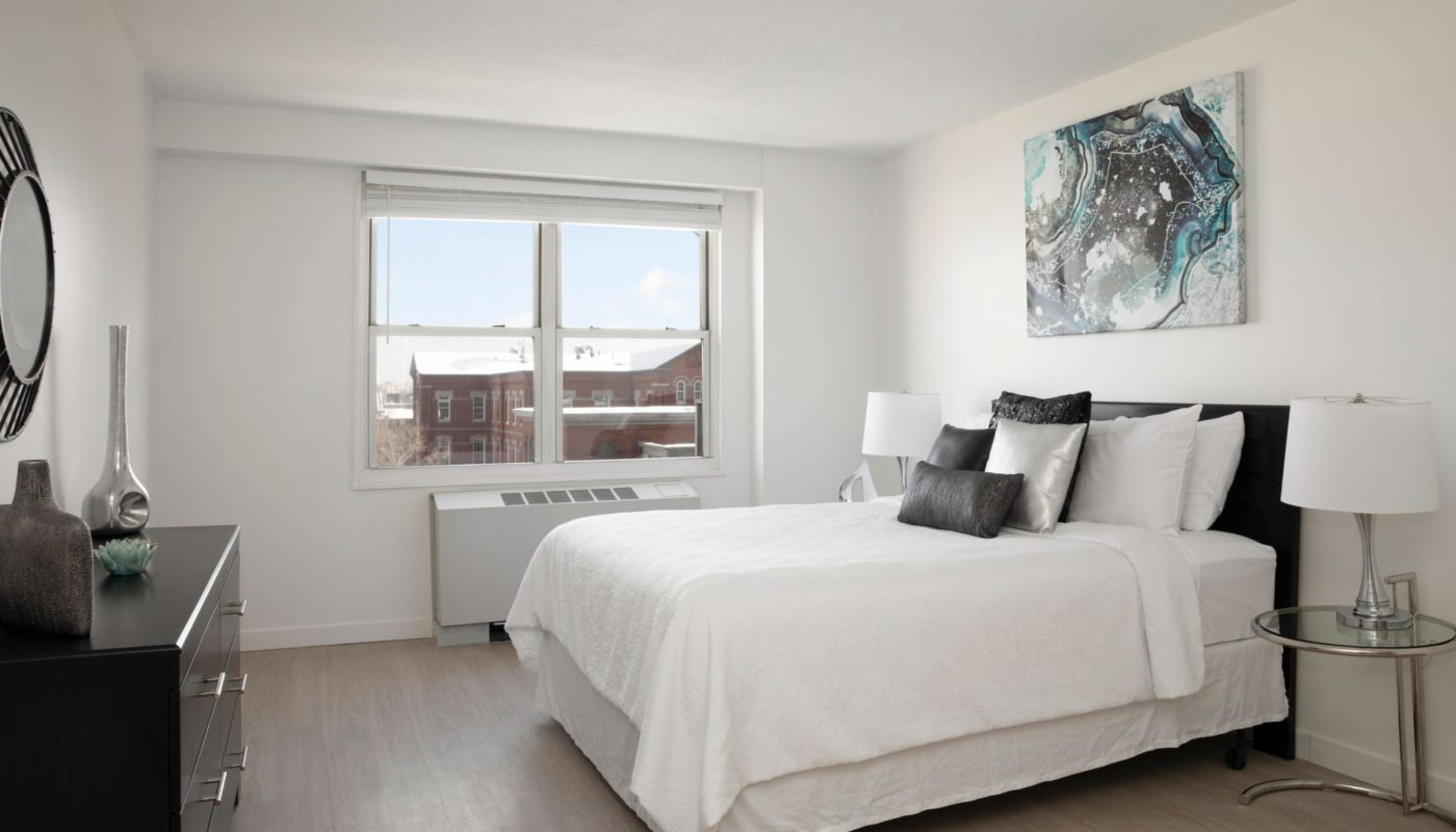 Bedroom with bed, dresser, mirror, night stand, modern artwork and large window in boston ma