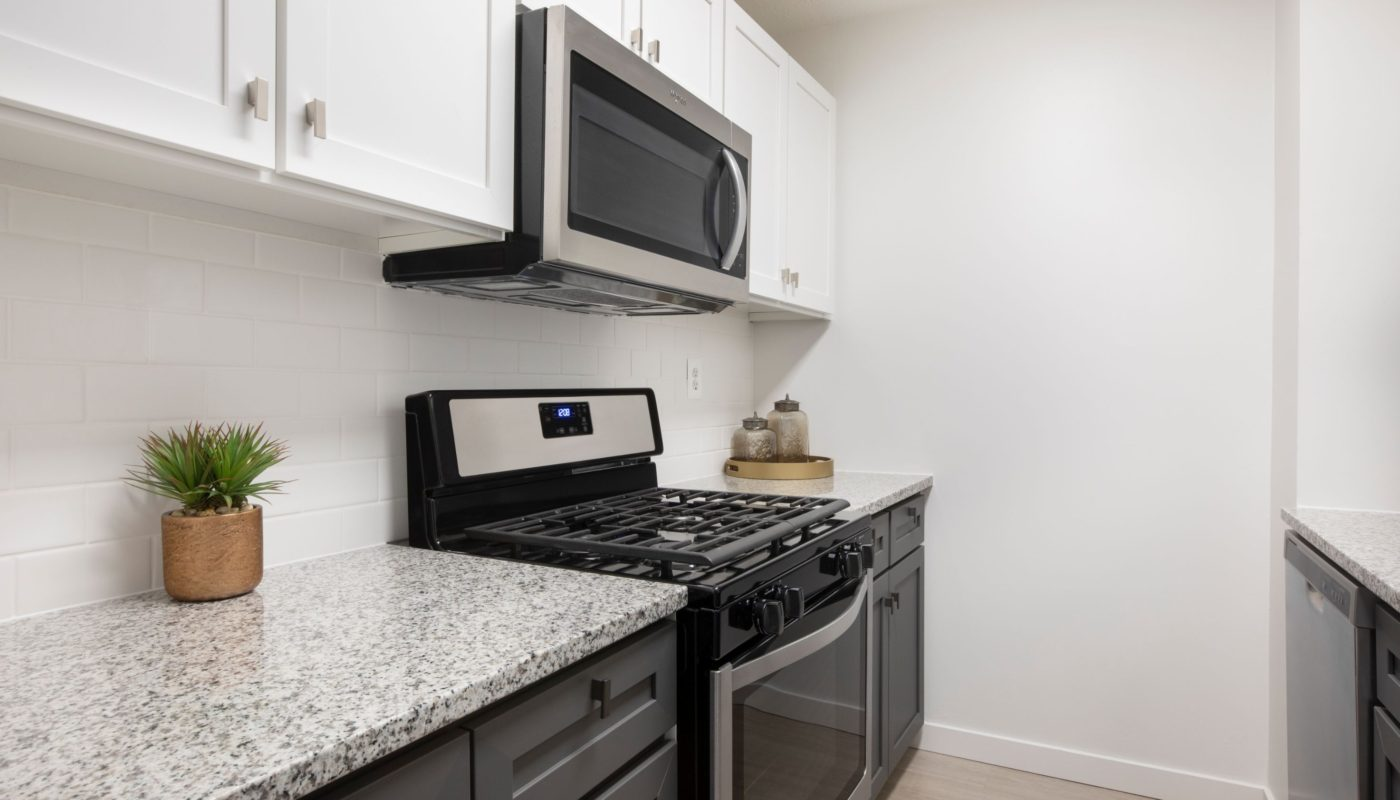 kitchen with granite counters and stainless steel appliances at j vue boston high rise apartments