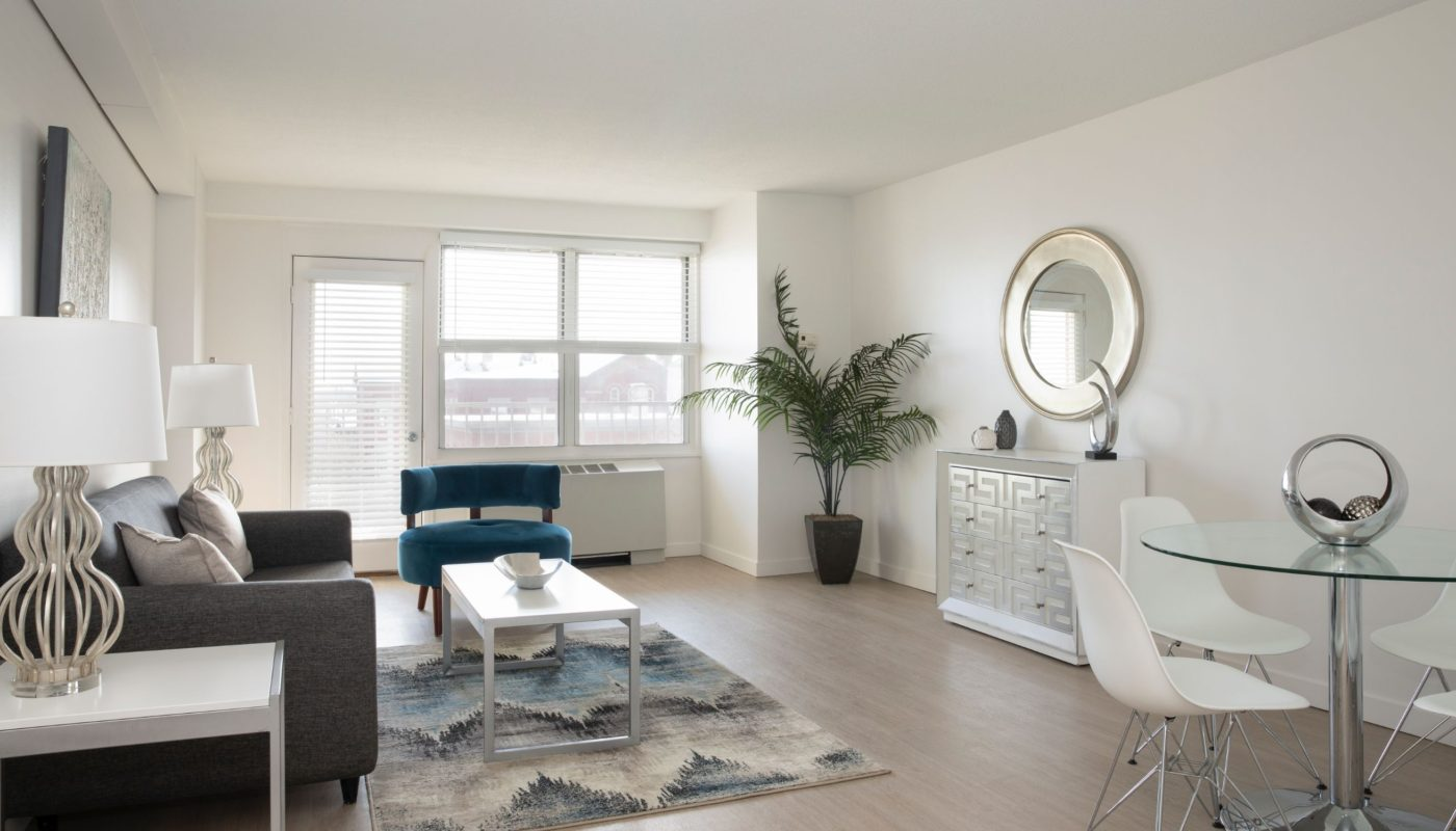 living area with sofa, coffee table, end tables, large windows and dining area a boston apartment