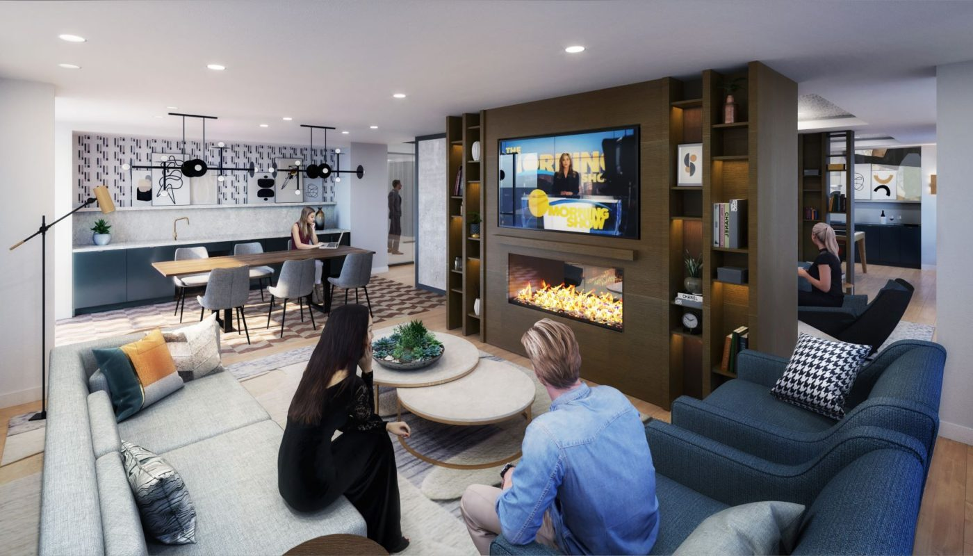 people socializing in a lounge with kitchen, remote work space, social seating, a fireplace and large flat screen tv at j vue luxury apartments in boston