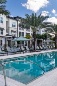exterior of 3 story apartment building with screened in balconies and view of pool at jefferson lake howell luxury apartments in Casselberry