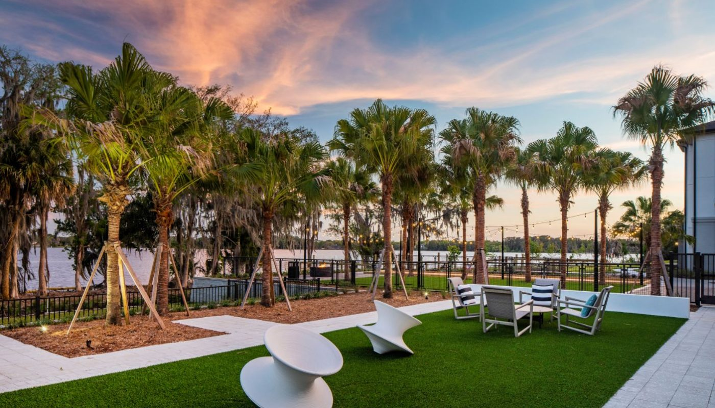 courtyard, palm trees, modern art, table, chairs and view of pool at a Casselberry luxury apartment
