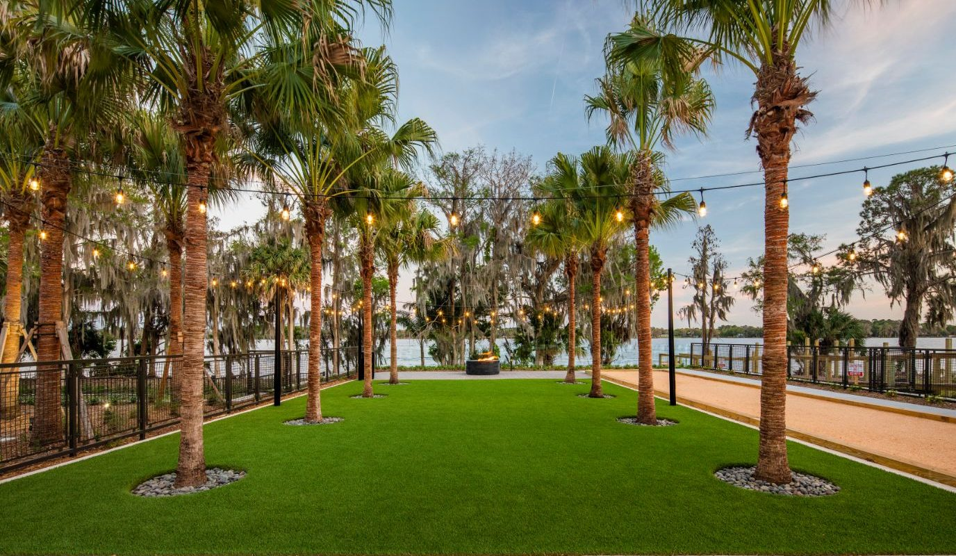 courtyard with palm trees, bocce ball court, fire pit, and view of lake in casselberry fl