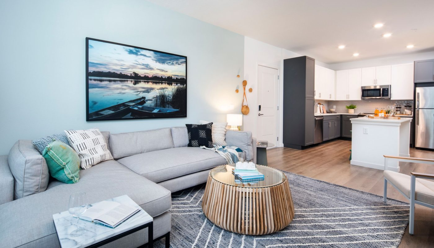 living space with sectional sofa, coffee table, end table, modern artwork and view of kitchen jefferson lake howell luxury apartments in Casselberry