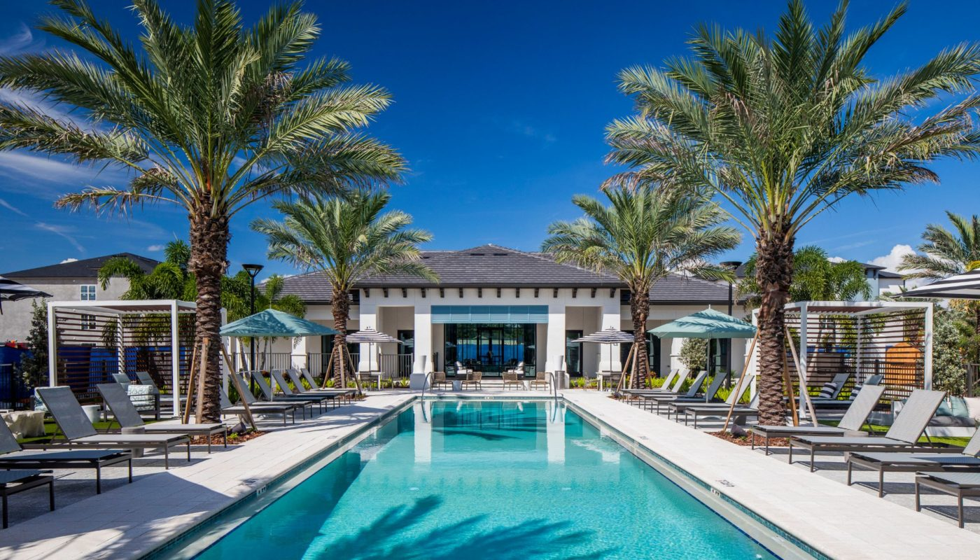 swimming pool with palm trees, lounge chairs, umbrellas and view of outdoor lounge at jefferson lake howell luxury apartments in Casselberry