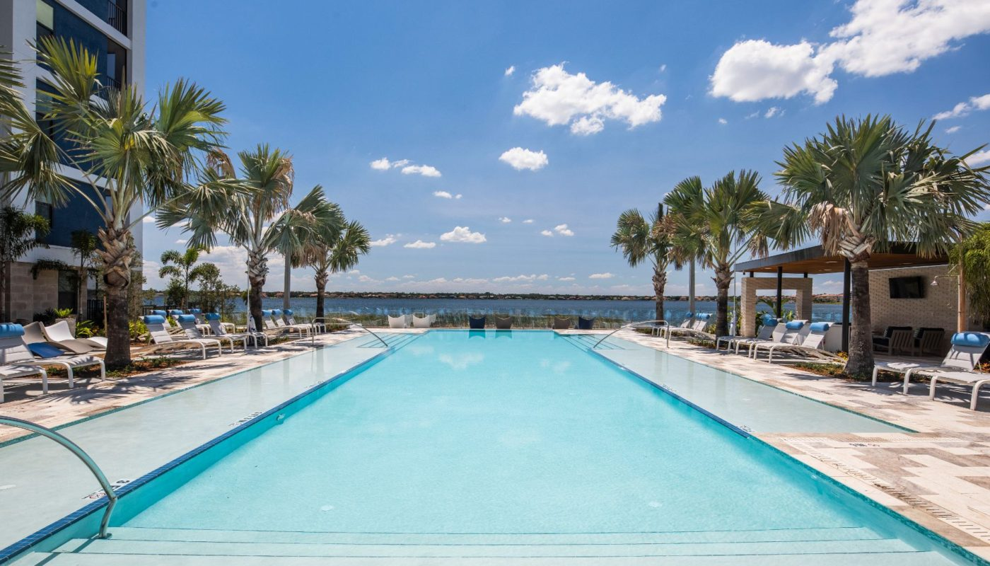 pool with chaise lounge chairs, palm trees and view of big sand lake at Orlando luxury apartments