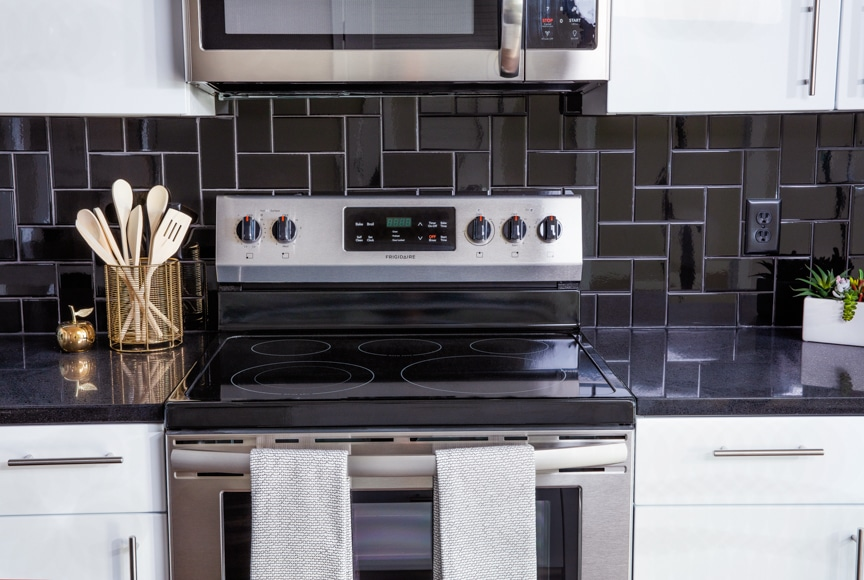 close up of glass top stove with microwave and tile backsplash at scout on the circle luxury apartments in fairfax va