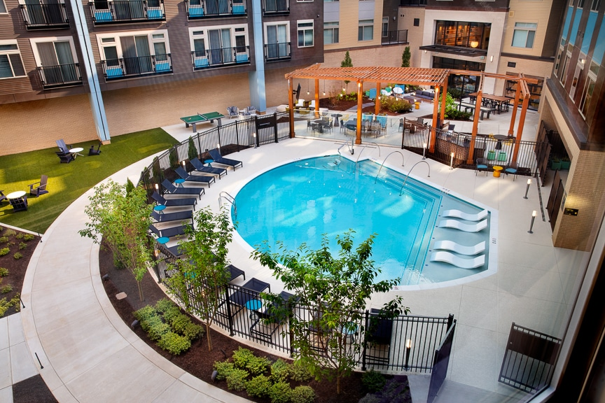 pool with lounge chairs, lush landscaping, pergola, social seating and grills at scout on the circle fairfax luxury apartments