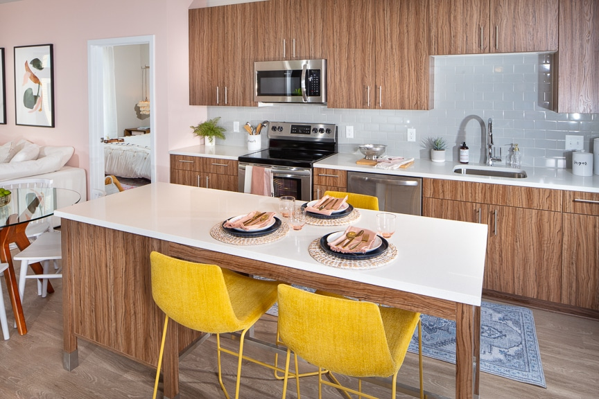 kitchen with moveable island, stainless steel appliances, wood cabinetry, quartz counters, tile backsplash and views of the bedroom and living area at scout on the circle luxury fairfax apartments