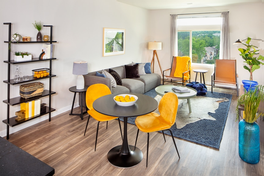 living area with couch, coffee table, dining area, bookshelves, greenery and large window, at scout on the circle fairfax luxury apartments