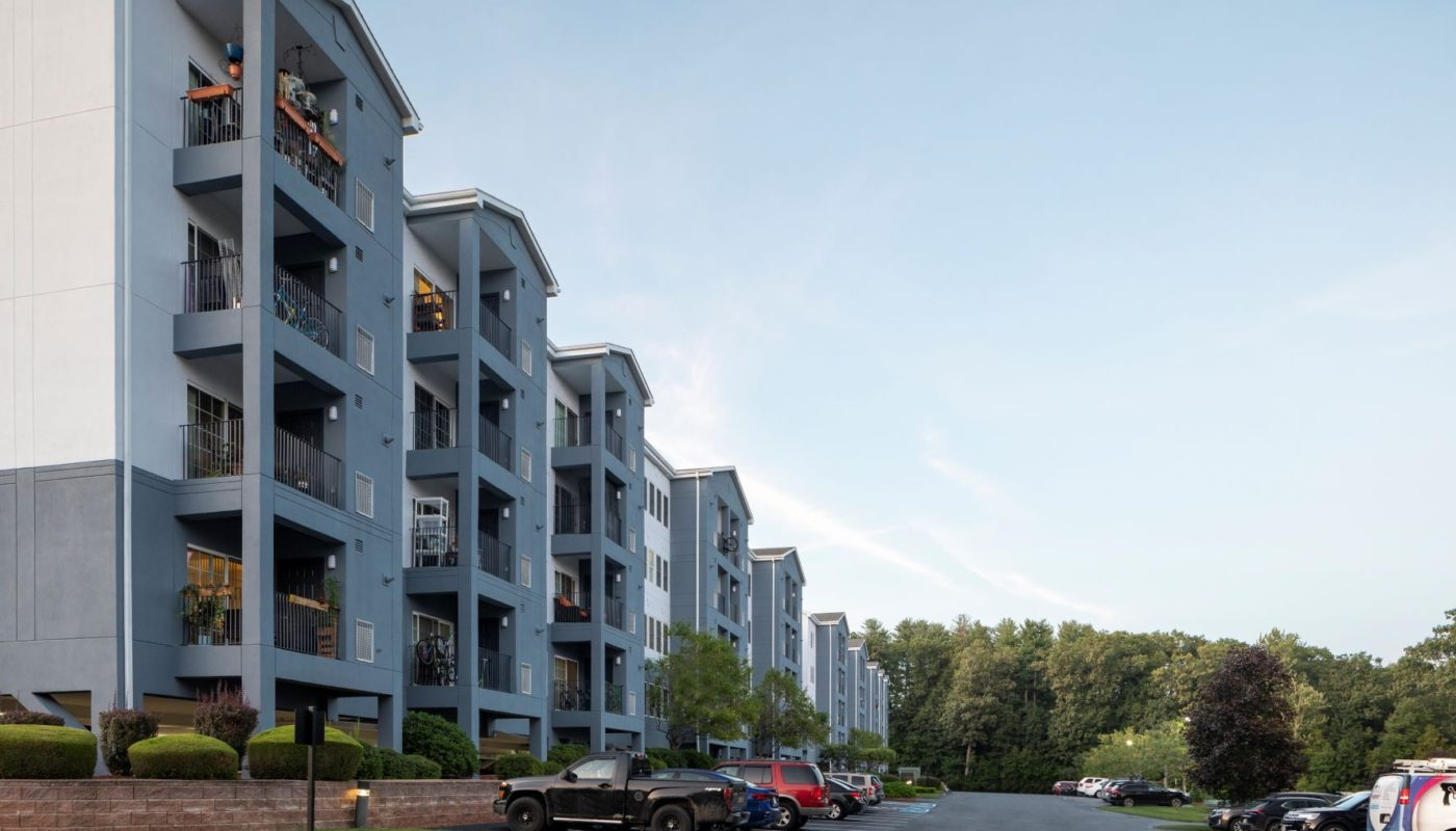 exterior apartment building with lush landscaping at j highlands at hudson apartments