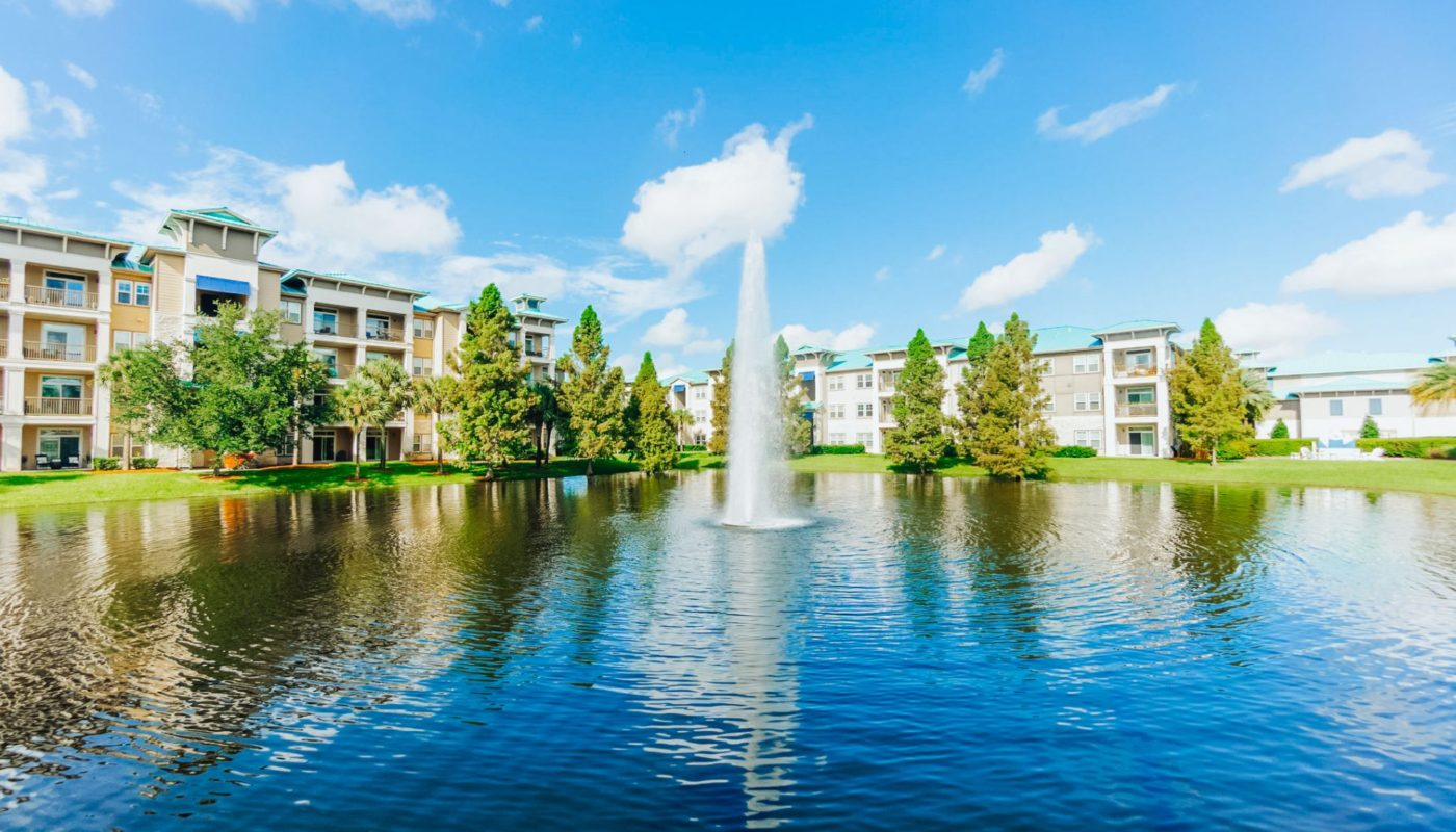 fountain in pond in front of sea isle orlando luxury apartments